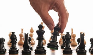 A hand moving a chess piece during a game