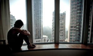 a lonely girl looking out of a high rise flat