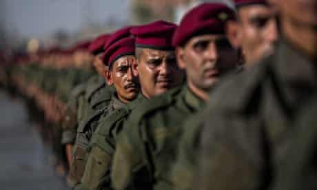 Iraqi volunteers in the newly formed 'Abbas Brigades' parade in the holy Shia city of Karbala