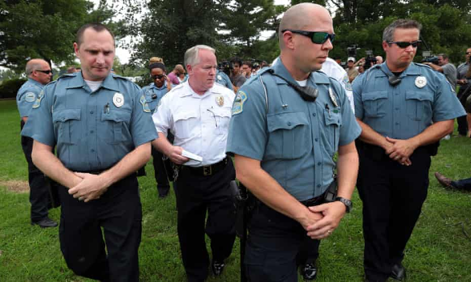 Ferguson Police Chief Tom Jackson leaves a news conference in Forestwood Park.