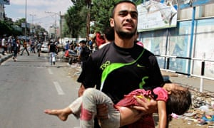 A Palestinian man carries a child killed in the blast outside a UN run school in Rafah, in the south