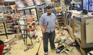 Business owner Mustafa Alshalabi cleans up his store, Sam's Meat Market, after it was looted during another night of rioting in Ferguson.