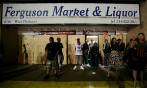 People stand in front of a convenience store, scene of an alleged theft of cigars by police shooting victim Michael Brown, after it was looted early Saturday.