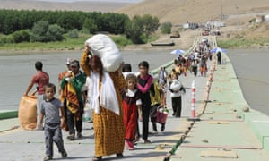 Displaced members of the Yezidi community carrying goods and food cross the Tigris river as they make their way from Syria into Iraq.