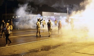 Demonstrators react as the police fire tear gas.