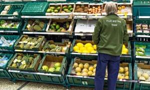 Supermarket worker at fruit and vegetable shelves
