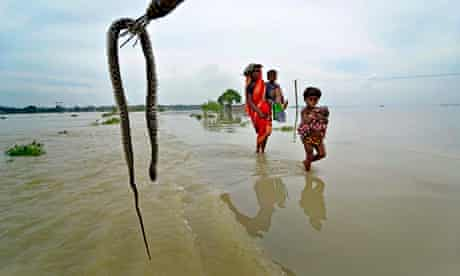 Nepalese villagers walk through floodwaters in Banke