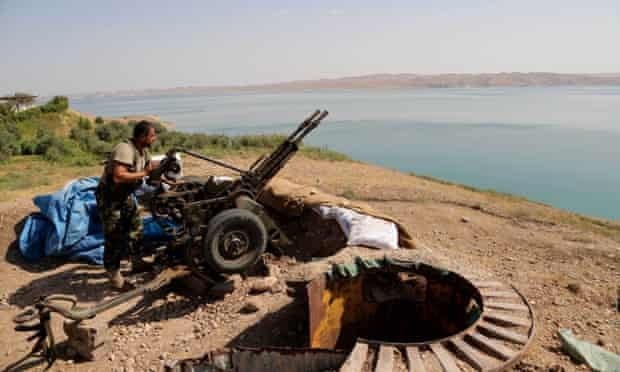 A Kurdish peshmerga fighter prepares his weapon at his combat position near the Mosul Dam at the town of Chamibarakat outside Mosul, Iraq. Kurdish forces took over parts of the largest dam in Iraq on Sunday less than two weeks after it was captured by the Islamic State.