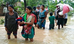 Nepalese villagers carry their belongings through flooded streets