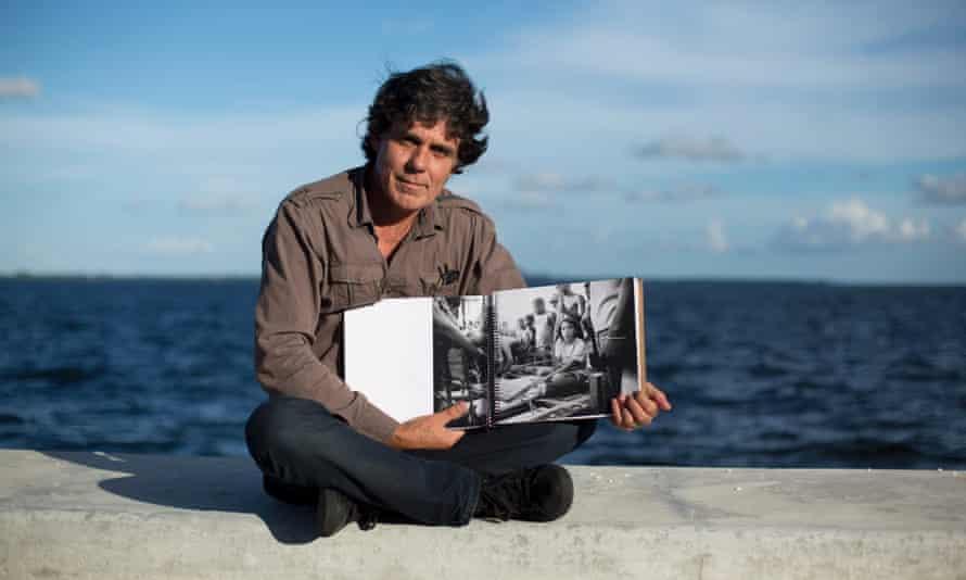 William Castellanos displays a book of his photos in Miami.
