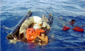 In this 11 September 1994 photo, three refugees cling to their overturned raft and life preservers as the US coast guard moves in to pick them up approximately 15 miles north of Cuba.
