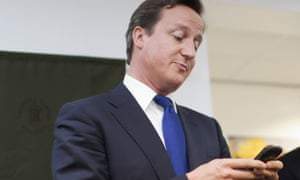 David Cameron reading from his Blackberry during a school visit in 2011.