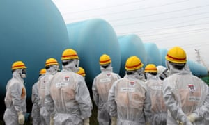 Members of the Japan Nuclear Regulation Authority  inspect makeshift water storage tanks at the Fukushima nuclear power plant.