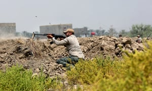 An Iraqi Shia fighter fires his weapon during clashes with militants from the Islamic State group in