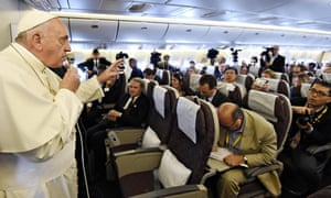 Pope Francis gestures while aboard a flight
