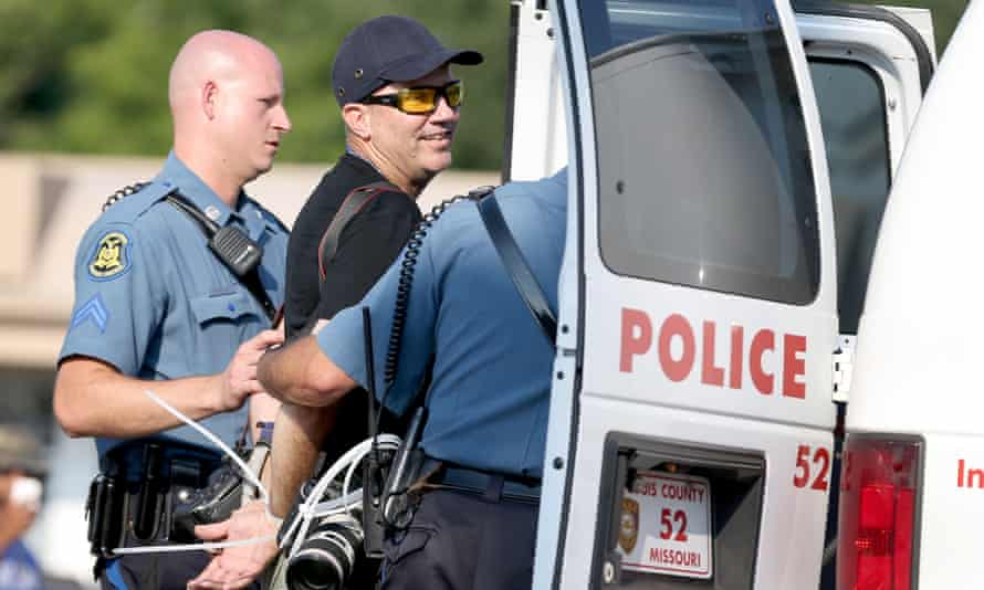 Scott Olson is placed into a police vehicle after being arrested while covering demonstrations in Ferguson.