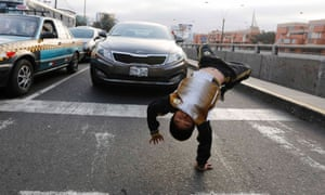 Nine-year-old Gianpierre somersaults at a traffic junction in the San Borja district in Lima.