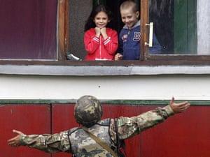 A Ukrainian soldier gestures as he talks with children in Popasna