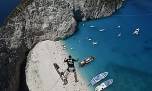 Lukas Michul, a member of the 'dream walker' group jumps from atop the rugged rocks overlooking the azure waters of Navagio beach, one of the Greece's most renowned leisure spots