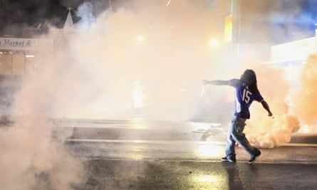 A demonstrator throws a grenade back at police after a brief clash on August 15, 2014 in Ferguson, Missouri.