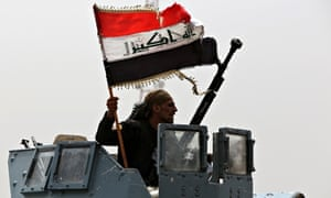 An Iraqi soldier waves the national flag