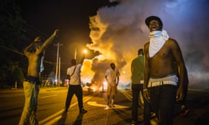 Demonstrators stand in the middle of West Florissant as they react to tear gas fired by police.