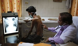 An Indian doctor examines a tuberculosis patient