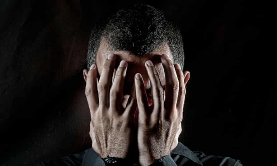 Depressed man with head in hands