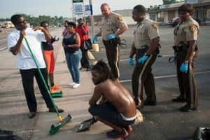 St Louis County Police join volunteers to clean up debris from continued overnight unrest in the streets of Ferguson.