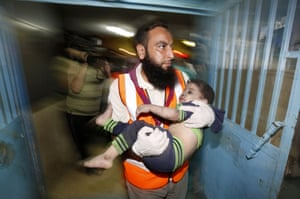 Palestinian doctor carries a wounded child at the Shifa hospital following an Israeli air strike on a house in Gaza City. The Israeli air strike killed a young girl and a woman, wounding 16 other people.