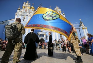 An orthodox priest prays with volunteers of the battalion 'Donbas' during a blessing ceremony in St. Michael Cathedral in Kiev, Ukraine.