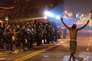 A protestor holding his hands up chants 'Hands up, don't shoot' as SWAT police unit stands guard during protests against police killing of Michael Brown in Ferguson, Missouri, United States.