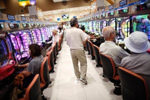 Visitors play pachinko in rows, seated
