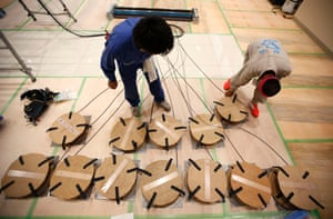 Workers check electrical cables to be used for security cameras during construction work for the opening of a Pachinko parlour in Fukaya, north of Tokyo.