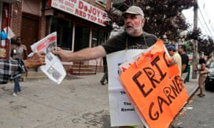 Doug Phaneuf hands a newspaper to a pedestrian while offering information to passersby about a rally for Eric Garner on Friday in Staten Island, New York.