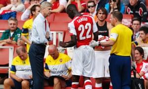 Arsenal's Yaya Sanogo leaves the pitch after tweaking something.