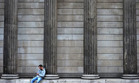 A man checks his phone outside the Bank