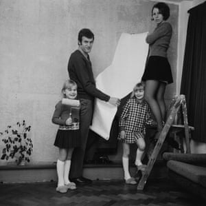 Gordon Bolland of Millwall decorates a room in his house with his wife and children.
