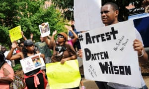 Protestors at the St Louis County Justice Center in Clayton, Missouri call for the arrest of Police Officer Darren Wilson.
