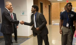 Attorney general Eric Holder, left, shakes hands with Bradley J. Rayford, 22, right, following his meeting at Florissant Valley Community College.