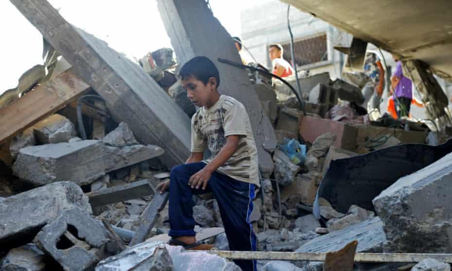 A Palestinian boy surveys damage after another night of air strikes on Gaza.