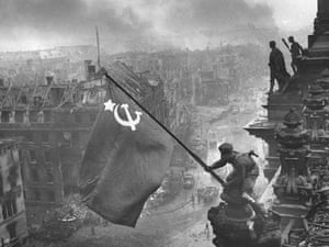 Russian soldiers flying the Red Flag, made from table cloths, over the ruins of the Reichstag in Berlin, 1945.