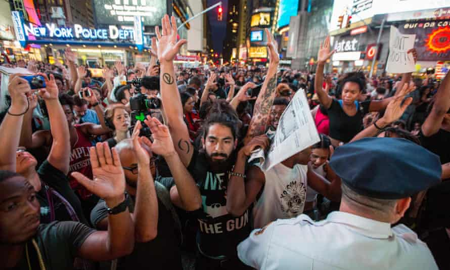 Protesters hold up their arms during a peaceful demonstration in New York City's Times Square on 14 August 2014.