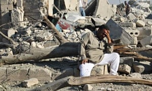 A Syrian man cries as he sits on the rubble Aleppo
