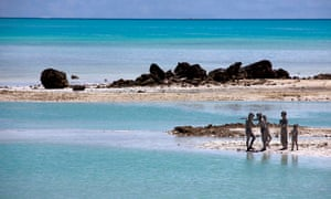 kiribati Young boys cover each other in reef-mud