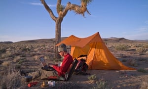 A man working on a laptop while camping in the desert in Death Valley CA