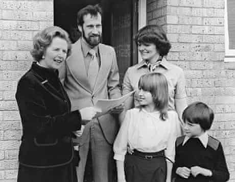 British Prime Minister Margaret Thatcher hands over the deeds to the council house belonging to the