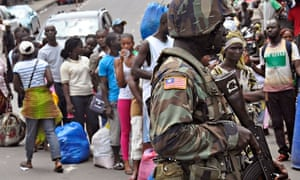 Liberia soldier scans people for signs of Ebola infection as part of quarantine measures in Monrovia