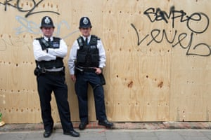 Police stand beside hoarding put up for the Notting Hill Carnival family day.