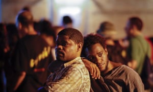 Local residents Vawone Duncan right) leans on his father Ducan Yawan in Ferguson.